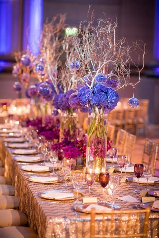 violet-hydrangeas-in-glass-column-vases-with-branches-and-glass-orbs-sequinned-patterned-linens