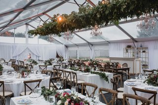 wedding-reception-tent-clear-top-wood-vineyard-chairs-greenery-chandelier-low-centerpieces