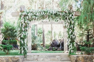 calamigos-ranch-wedding-wooden-ceremony-arch-with-wisteria-greenery