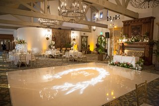reception-ballroom-wood-beams-chandeliers-white-dance-floor-with-projection-wreath-motif-gobo