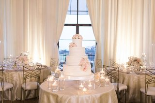 wedding-cake-white-four-layer-confection-fresh-flowers-pink-white-blooms-floating-candles