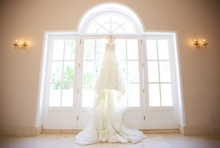bridal-gown-with-cathedral-length-train-hanging-from-top-of-window-door-at-chateau-wedding-venue