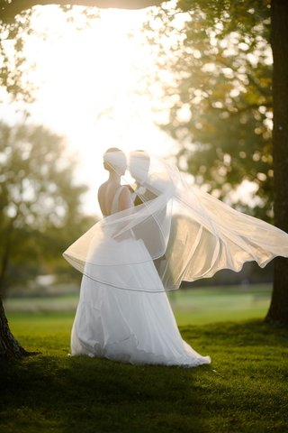 bride-in-a-line-wedding-dress-with-low-back-and-classic-veil-groom-in-tuxedo-portrait-ideas