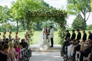 bride-in-a-fit-and-flare-vera-wang-dress-ruffled-skirt-veil-groom-in-white-tux-jacket-at-outdoor