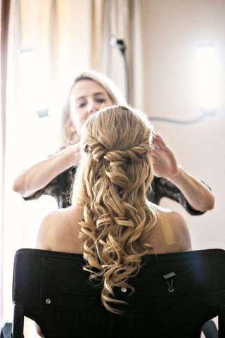 bride-in-bridal-suite-getting-ready-with-professional-hair-stylist-and-makeup-artist-curls-half-up