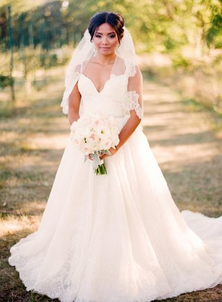 bride-in-a-lace-dress-with-spaghetti-straps-and-veil-with-floral-details-holds-a-bouquet