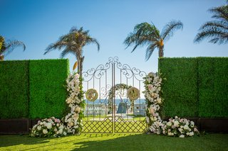wrought-iron-gate-ceremony-couples-initials-florals-white-pink-greenery-beach-hotel-del-coronado