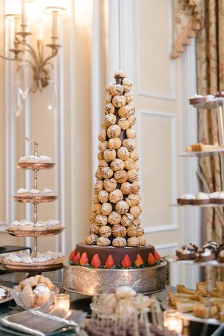 wedding-dessert-table-croquembouche-on-top-of-chocolate-layer-with-strawberries-pastry-stand-tiers
