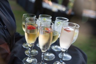 server-holding-tray-with-champagne-flutes-and-strawberry-slices