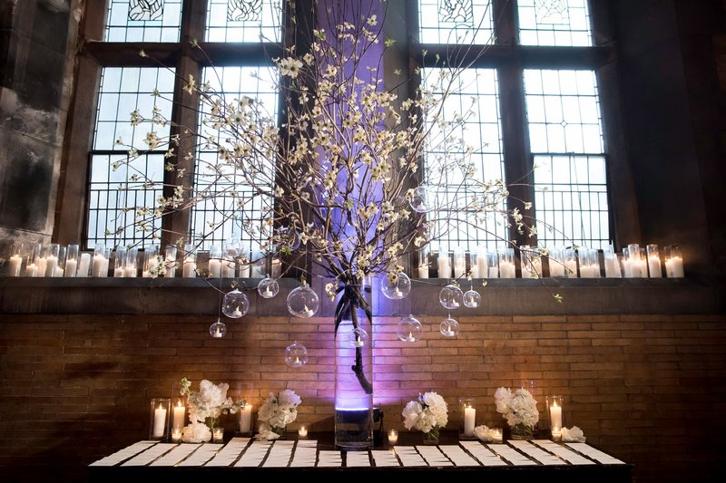 Escort Card Table in Front of Arch Windows