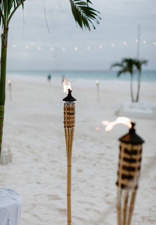 wedding-reception-on-beach-in-the-bahamas-tiki-flame-torches-on-sand-string-lights
