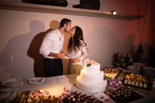 bride-and-groom-kiss-behind-their-small-three-tiered-wedding-cake-after-cutting-it
