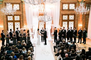 wedding-ceremony-with-tall-white-drapery-chandeliers-bridesmen-bridesmaids-and-groomsmen-rustic