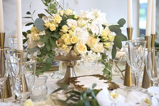 centerpiece-in-gold-container-small-yellow-roses-white-flowers-eucalyptus-leaves-ivy
