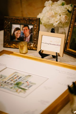 wedding-hashtag-and-gold-framed-photo-with-signatures-in-mat-picture-frame-of-couple-at-reception