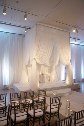 white-drapery-on-four-poster-wedding-structure-in-ballroom