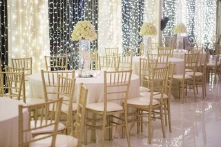 white-round-wedding-reception-table-gold-chairs-and-tall-vase-filled-with-white-orchid-rose-flowers