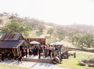 wedding-guests-mingling-on-wooden-deck