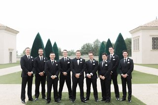 groom-and-groomsmen-in-black-tuxedos-with-ties-groom-in-bow-tie-white-flower-boutonniere
