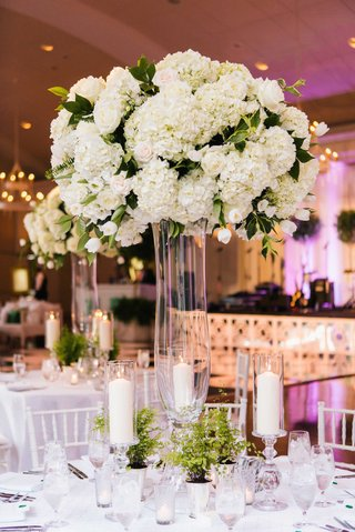 clear-glass-riser-with-white-arrangement-of-hydrangea-flowers-rose-tulip-and-green-leaves