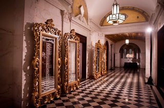 ornate-gold-mirror-frames-in-black-and-white-checkered-floor-hallway-at-vibiana-with-seating-chart