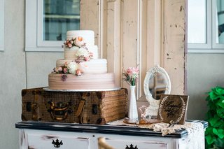 an-ombre-wedding-cake-in-white-and-pink-with-fresh-flowers-vintage-luggage-case-antique-items