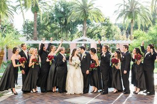 wedding-party-cheers-bride-groom-black-dresses-suits-red-bouquets-ivory-wedding-dress-florida