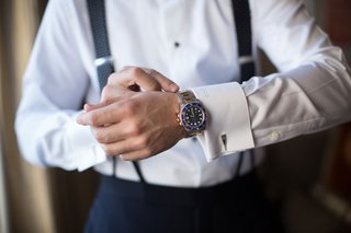 groom-tightening-watch-cuff-links-and-monogrammed-cuffs-white-shirt-suspenders