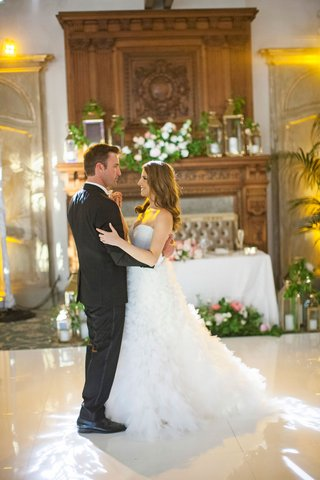 bride-in-monique-lhuillier-wedding-dress-dancing-with-groom-indoor-reception-white-dance-floor