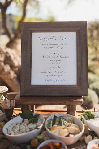 cocktail-hour-mozzarella-bar-at-outdoor-wedding-rustic-wood-frame-with-calligraphy-sign-laura-hooper