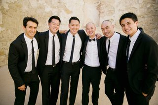 groom-in-black-tuxedo-and-bow-tie-groomsmen-in-tuxedos-and-black-skinny-ties