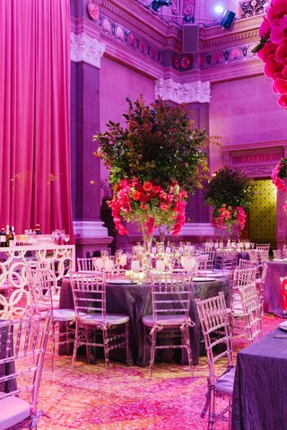 round-wedding-table-with-tall-greenery-orchid-carnation-and-orchid-centerpiece-with-clear-chairs