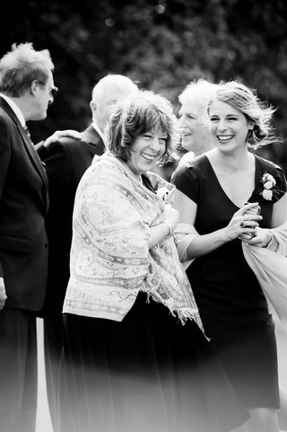 black-white-photo-of-smiling-mother-of-the-bride-and-sister-of-the-bride-in-wraps-on-a-windy-day