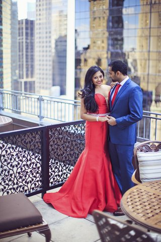 south-indian-couple-bride-in-red-wedding-gown-groom-in-blue-suit-with-red-tie
