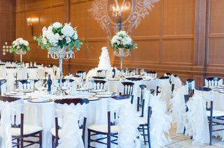lighting-projection-of-monogram-on-wall-round-tables-tall-centerpieces-white-chair-covers-ruffles