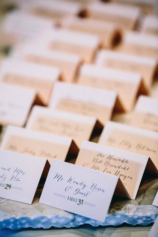 small-white-folded-escort-cards-featuring-calligraphy