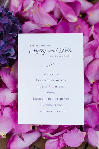 wedding-ceremony-program-card-on-bed-of-purple-fuchsia-flower-petals-simple-order-of-events