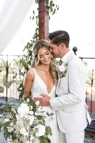 bride-in-v-neck-wedding-dress-long-hair-boho-style-groom-in-casual-suit-white-flowers-greenery