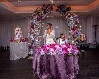 bride-and-groom-behind-purple-sweetheart-table-magenta-florals-on-top-floral-arch-behind