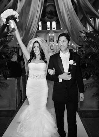 black-and-white-photo-of-bride-in-vera-wang-dress-and-groom-leaving-wedding-ceremony
