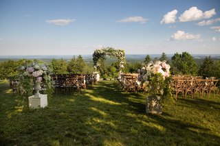 wedding-ceremony-arch-with-lots-of-greenery-wooden-chairs-floral-displays-forest-views