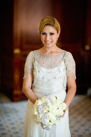 bride-in-jenny-packham-dress-with-beading-and-embroidery-holds-bouquet-of-white-roses-with-brooches