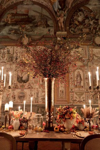 renaissance-inspired-tablescape-in-palace-in-florence-large-silver-vase-red-blossoming-branches