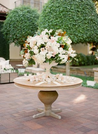 garden-wedding-reception-with-a-large-arrangement-of-white-and-pink-flowers-in-a-white-urn