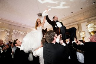wedding-reception-jewish-wedding-tradition-horah-dance-bride-groom-hoisted-on-chairs-at-reception