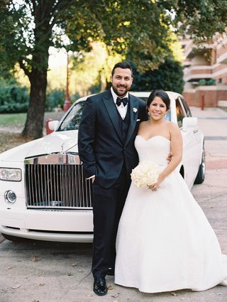 groom-in-tuxedo-and-bow-tie-bride-in-strapless-ball-gown-in-front-of-rolls-royce-wedding-car