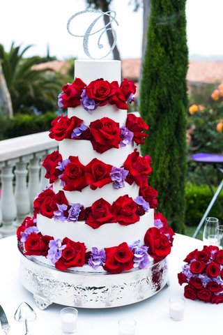 white-cake-with-red-roses-and-purple-flowers-on-tiers-and-crystal-c