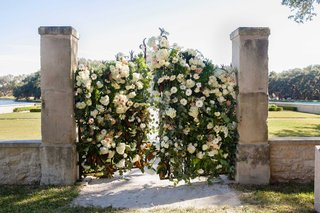 outdoor-wedding-ceremony-stone-wall-with-wrought-iron-gates-covered-with-green-leaves-and-flowers