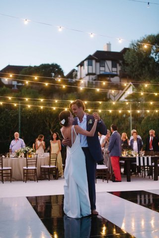 couple-dances-under-fairy-lights-black-white-dance-floor-oceanside-california-beach-wedding