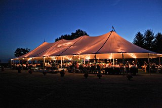farm-wedding-reception-in-an-open-sided-tent-lit-by-market-lights-at-sunset